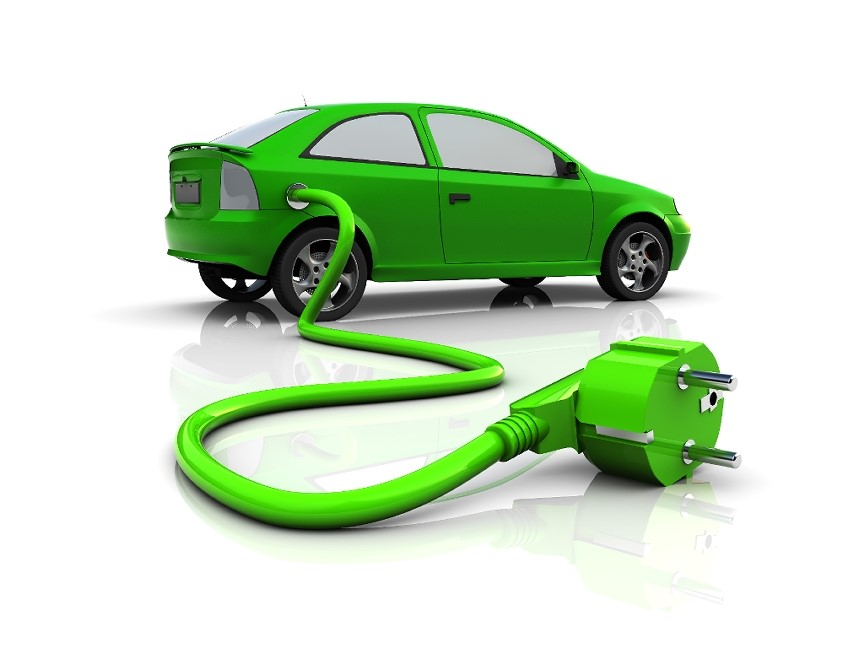 A green car with an electrical cord coming out of it
